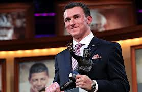 Manziel poses with the Heisman Memorial Trophy after winning the award for the nation's top College Football player as a Freshman out of Texas A&M (New York Times).